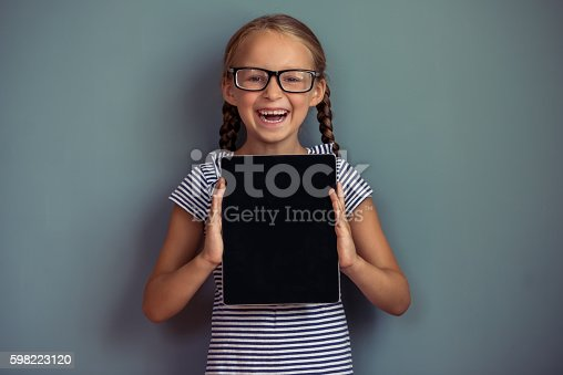 istock Cute little girl with gadget 598223120