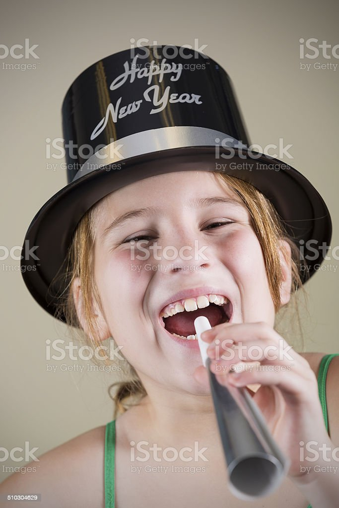 Cute little girl with Happy New Year hat and horn stock photo