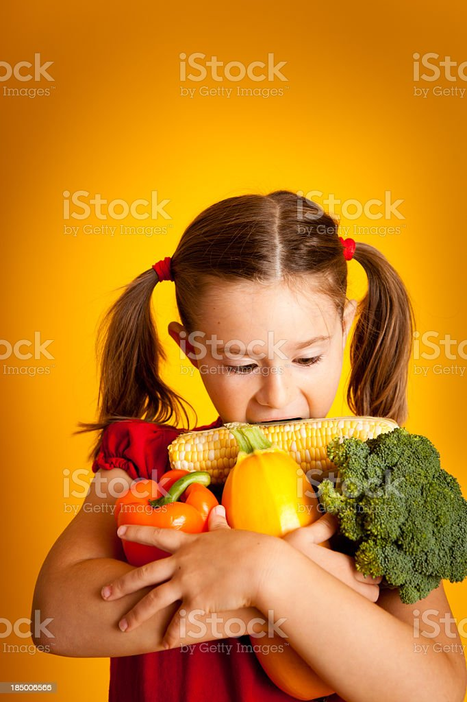 Cute Little Girl With Her Arms Full of Vegetables royalty-free stock photo