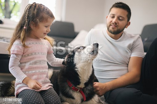 Cute little girl with her dog . Shallow DOF. Developed from RAW; retouched with special care and attention; Small amount of grain added for best final impression. 16 bit Adobe RGB color profile.
