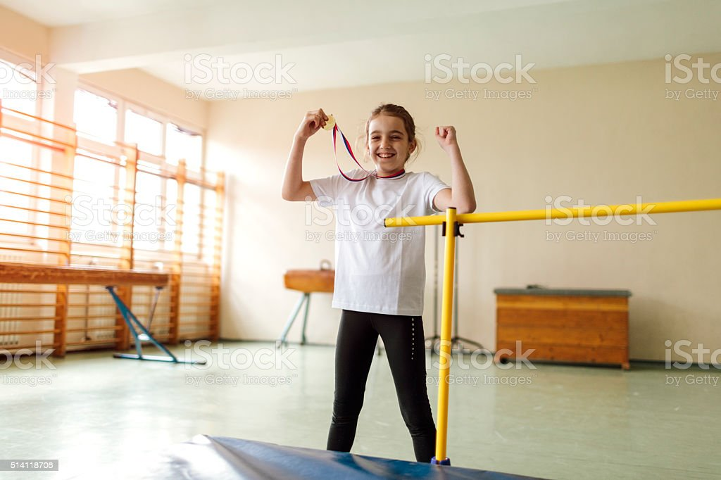 Cute Little Girl With Her First Gold Medal. stock photo