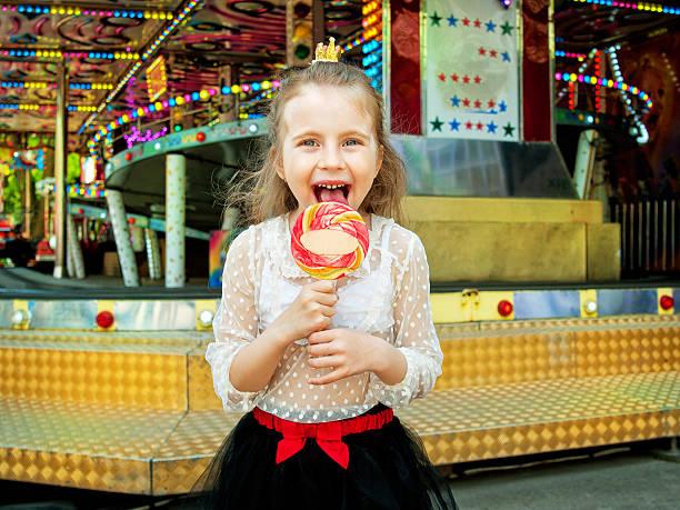 cute little girl with lollipop at amusement park - mini amusementpark stockfoto's en -beelden