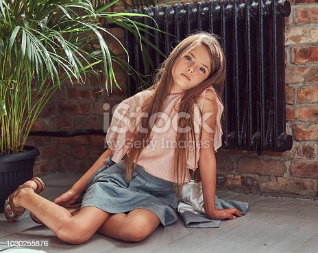 678651100 istock photo Cute little girl with long brown hair wearing a stylish dress, sitting on a wooden floor in a room with a loft interior 1030255876