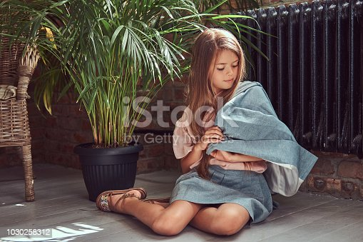 678651100 istock photo Cute little girl with long brown hair wearing a stylish dress, sitting on a wooden floor in a room with a loft interior 1030258312