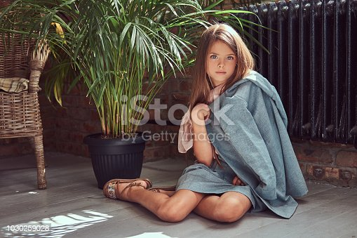 678651100 istock photo Cute little girl with long brown hair wearing a stylish dress, sitting on a wooden floor in a room with a loft interior 1030259028