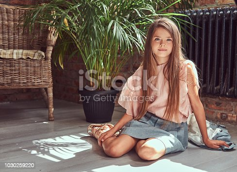 678651100 istock photo Cute little girl with long brown hair wearing a stylish dress, sitting on a wooden floor in a room with a loft interior 1030259220