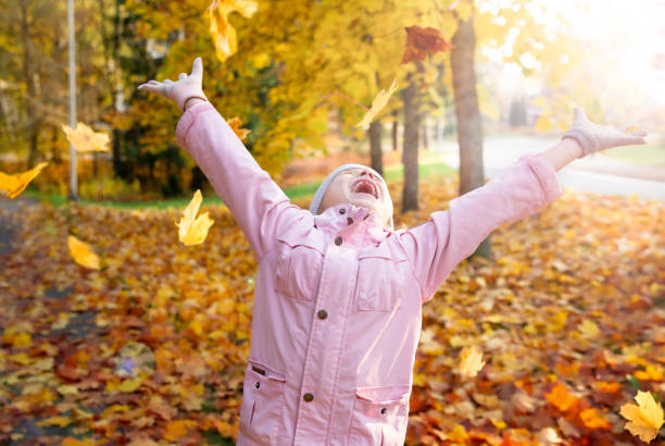 Cute little girl with missing teeth playing with yellow fallen leaves in autumn forest Cute little girl with missing teeth playing with yellow fallen leaves in autumn forest, trowing into the air. Happy child laughing and smiling. Sunny autumn forest, sun beam. autumn leaves child stock pictures, royalty-free photos & images