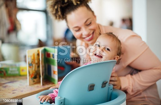 Cute little girl with mother at babies cafe. Daughter sitting on chair looking back and smiling, with mother sitting by holding a storybook.