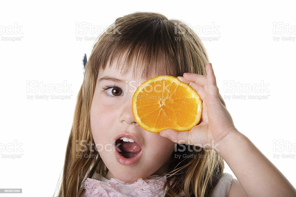 Cute Little Girl With Orange Slice over Her Eye royalty-free stock photo