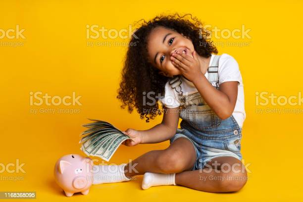 Cute little girl with piggy bank and banknotes yellow background picture id1168368095?b=1&k=6&m=1168368095&s=612x612&h=qsfcj984y9uewu txvggid zifw4qva50yn0otii8ei=