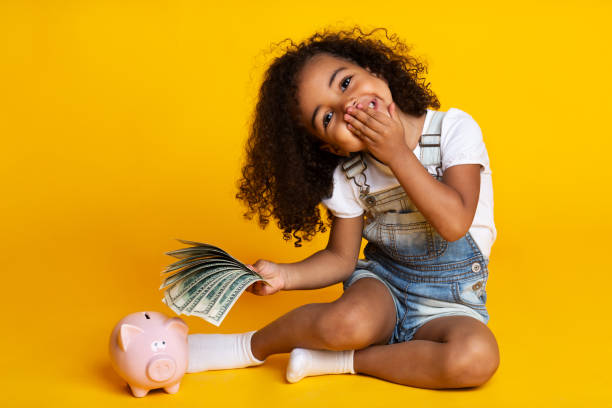 Cute little girl with piggy bank and banknotes yellow background picture id1168368095?b=1&k=6&m=1168368095&s=612x612&w=0&h=dmg1gprxwswex0nx 4e38d3kwvad5g3 zvop5vxq 0s=