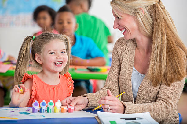 cute little girl with pigtails laughing while painting in daycare - pigtails stock photos and pictures