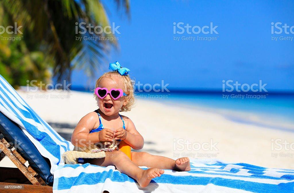 cute little girl with sunblock cream on beach stock photo