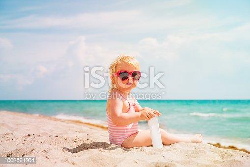 cute little girl with sunblock cream on tropical beach, sun protection