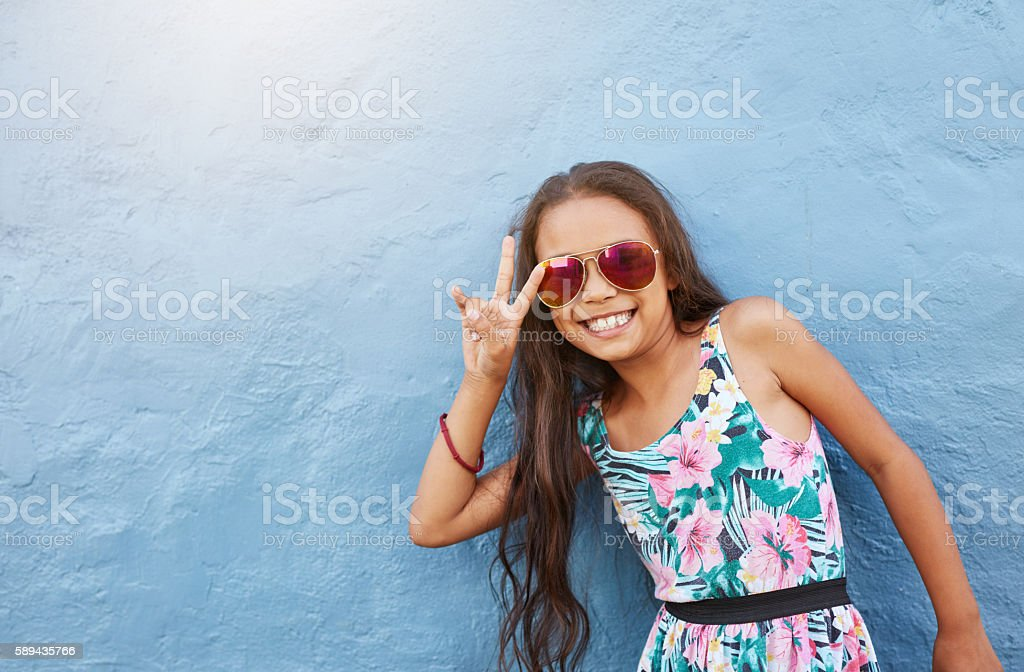 Cute little girl with sunglasses gesturing peace sign stock photo