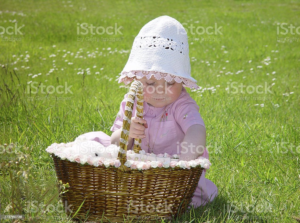 Cute little girl with teddy bear in basket Little 2 year old girl with hat putting bear to sleep in a basket. Affectionate Stock Photo