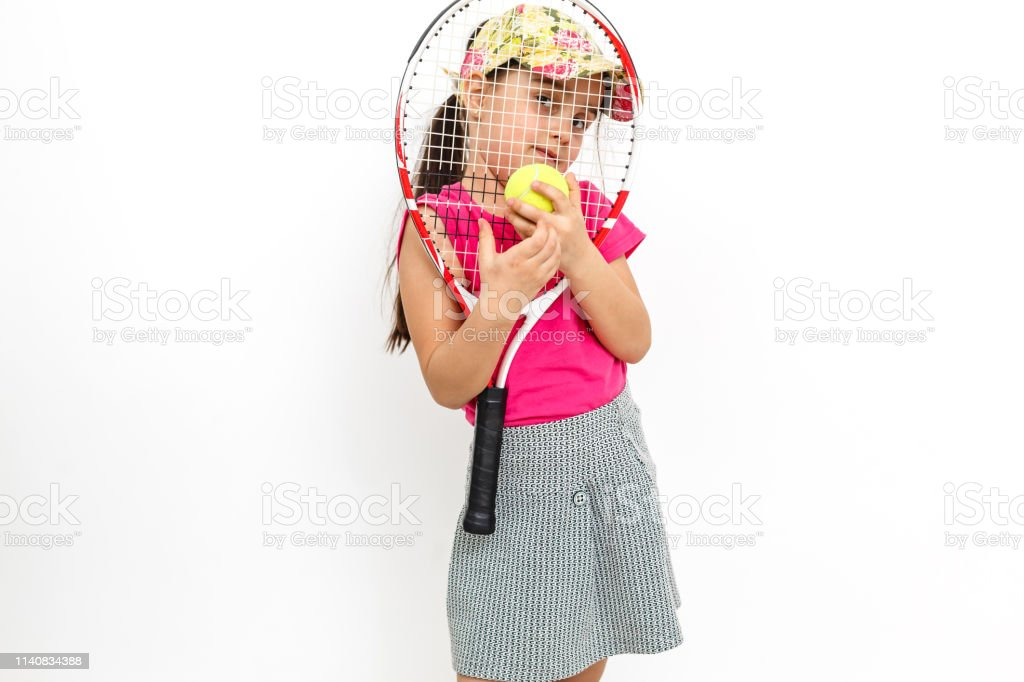 Cтоковое фото Cute little girl with tennis racket in her hands on white background