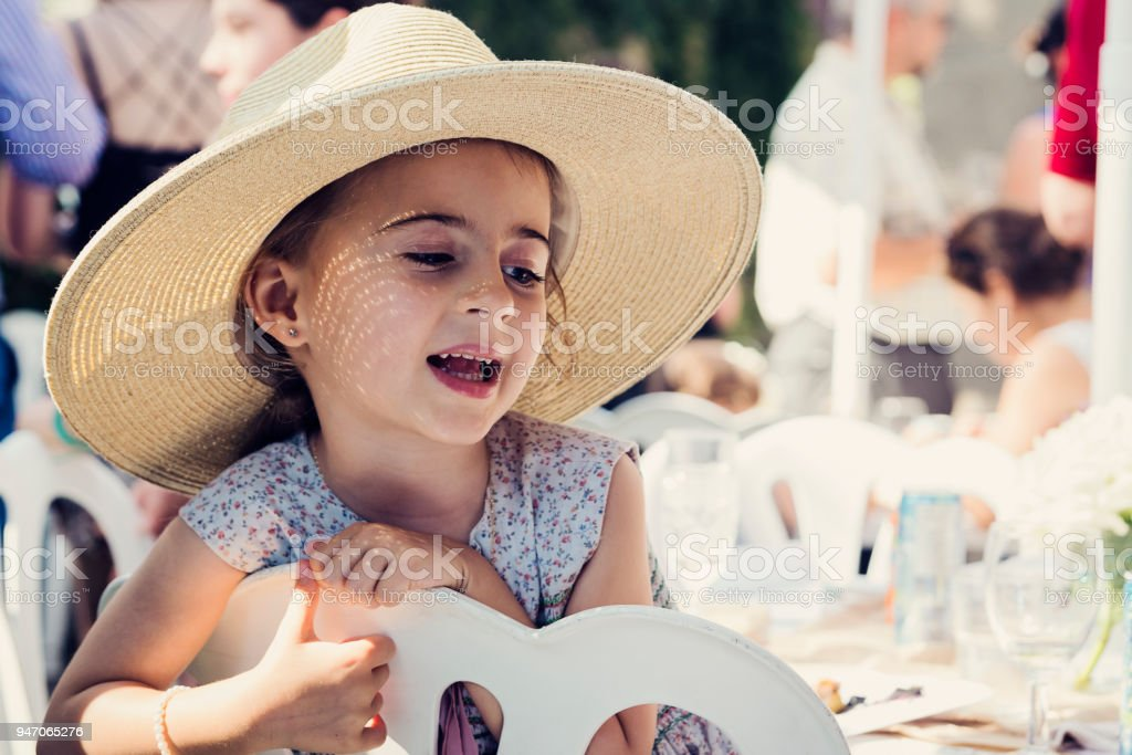 Cute little girl with too big at family reunion. stock photo