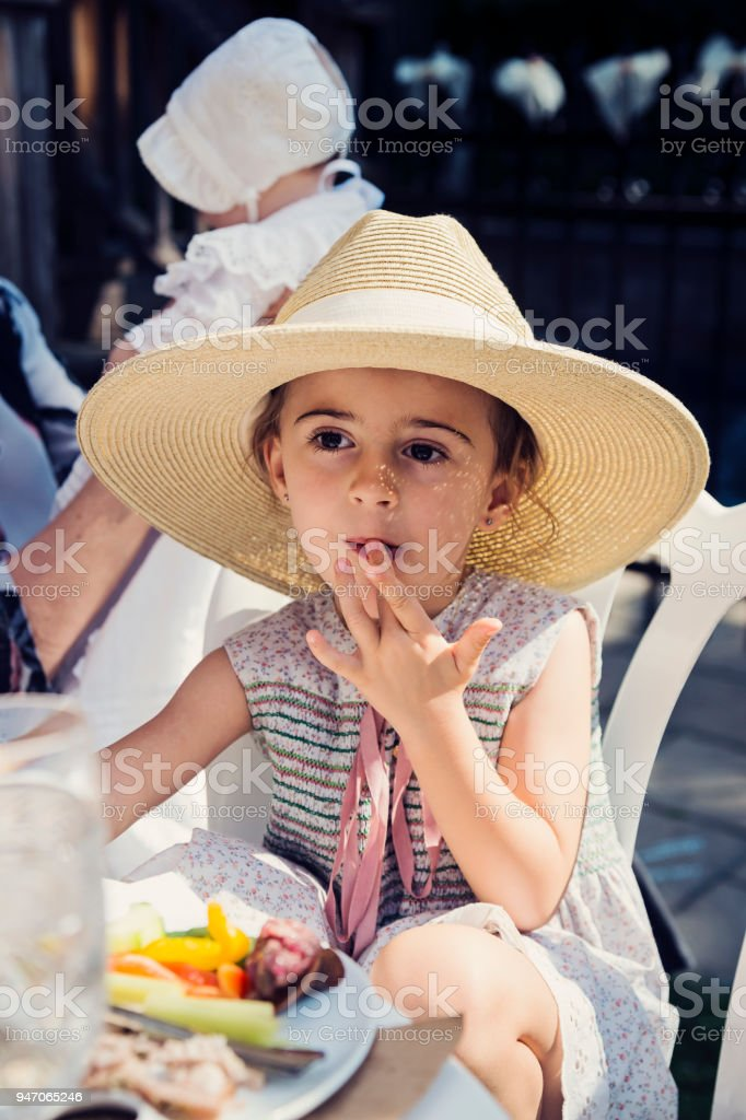 Cute little girl with too big hat eating outdoors at family reunion. stock photo
