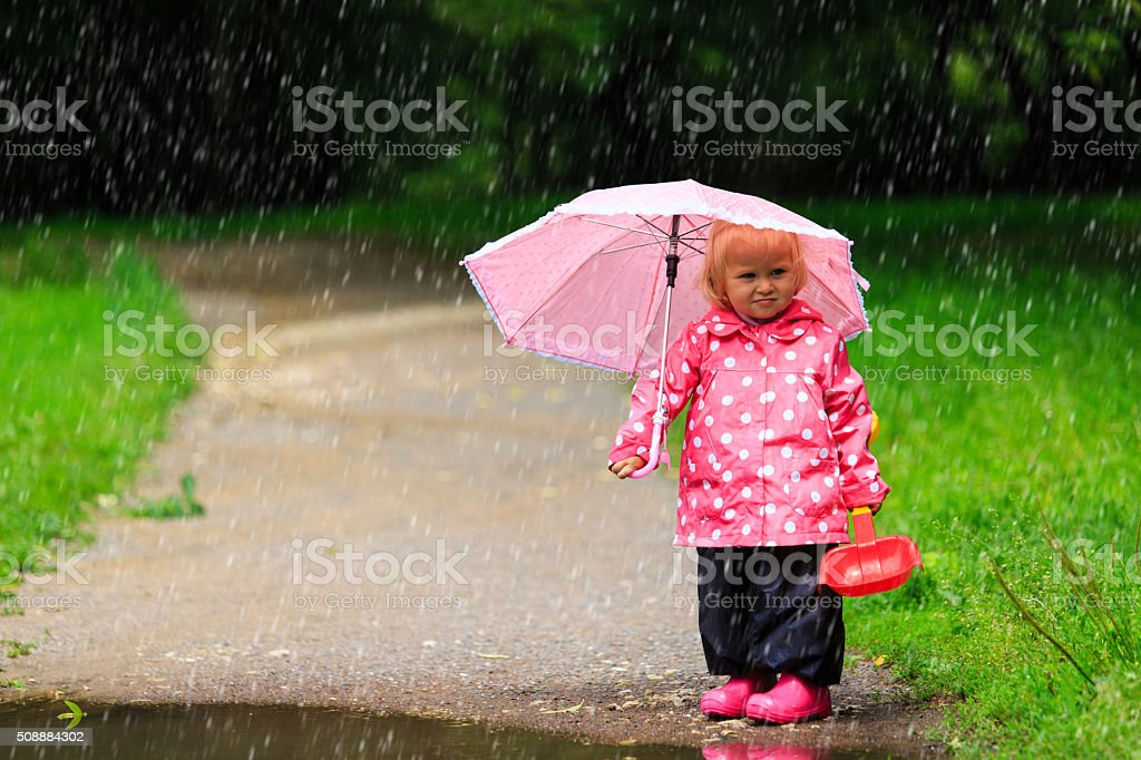 cute little girl with umbrella in raincoat and boots stock photo