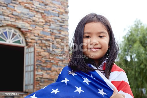 istock Cute little girl with USA flag in park 979885596