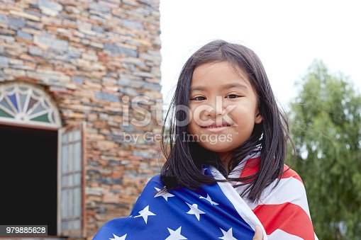 istock Cute little girl with USA flag in park 979885628