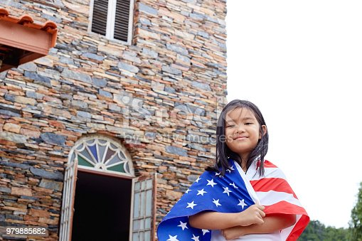 istock Cute little girl with USA flag in park 979885682