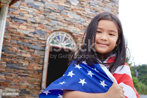 istock Cute little girl with USA flag in park 979885698