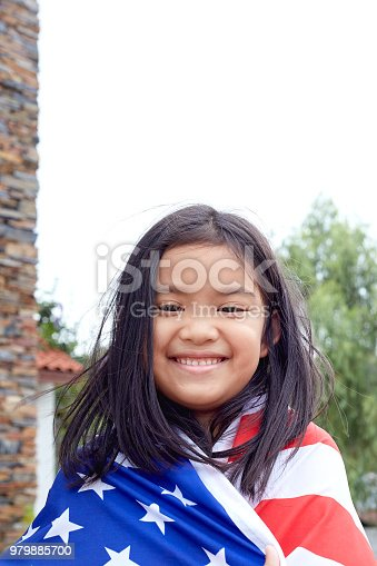istock Cute little girl with USA flag in park 979885700