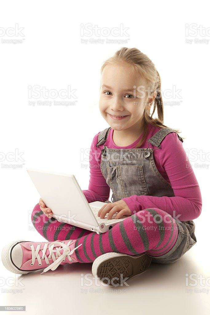 Cute little girl working on a notebook computer royalty-free stock photo