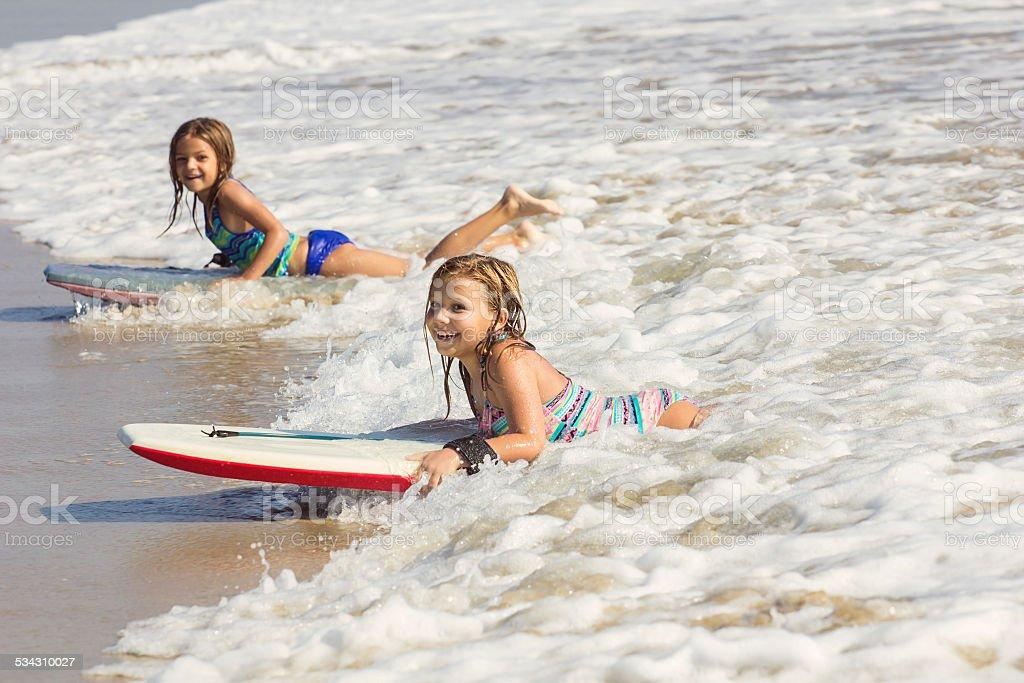 Cute little girls boogie boarding in the ocean waves stock photo