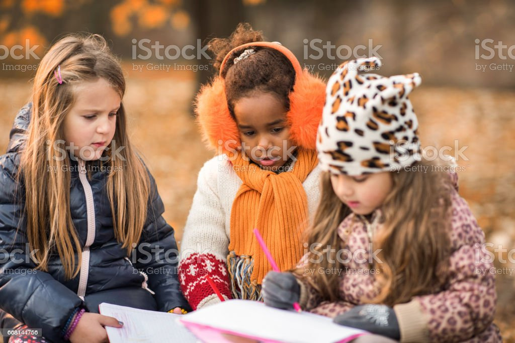 Cute little girls drawing in notebooks at the park. stock photo