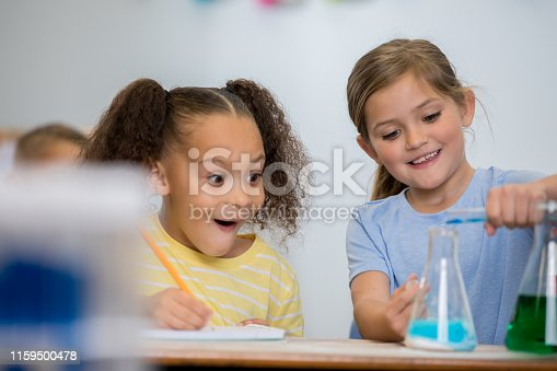 istock Cute little girls in science class smile excitedly while doing chemistry experiment 1159500478