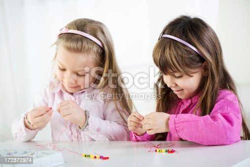 Two Cute little girls making bead Jewelry at home.