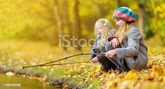istock Cute little girls playing by the water on beautiful autumn day. Happy children having fun in autumn park. 1169240448