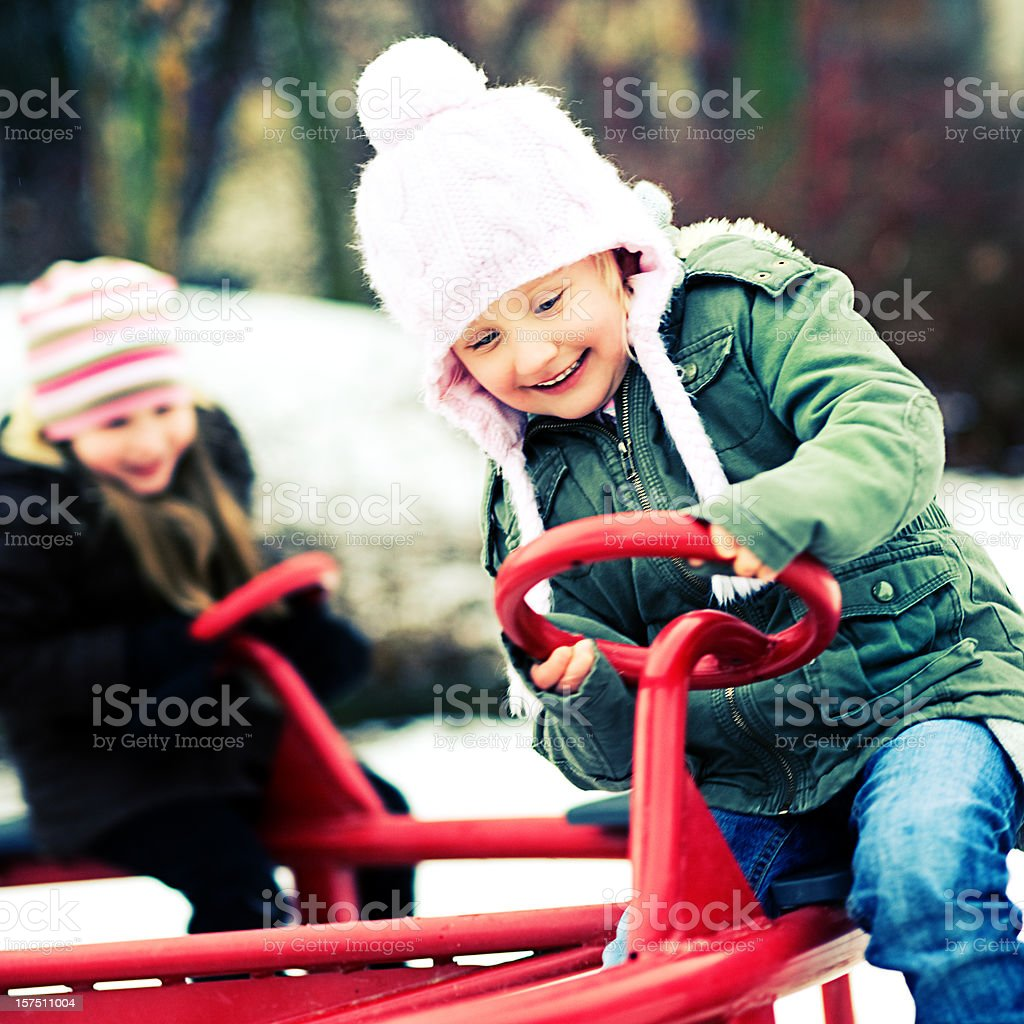 Cute little girls playing outdoors on a playground royalty-free stock photo