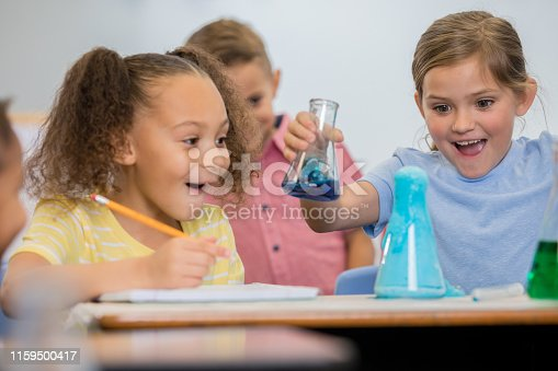 istock Cute little girls smile excitedly while doing science experiment in elementary STEM class 1159500417