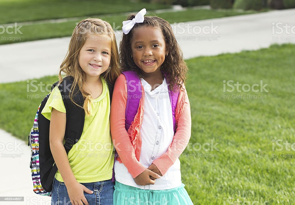 Cute Little girls walking to school together stock photo