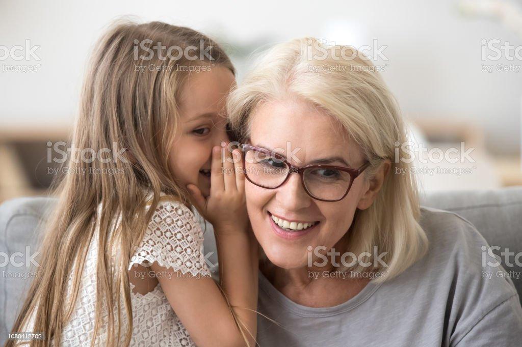 Cute little granddaughter whispering in ear telling secret to grandma royalty-free stock photo