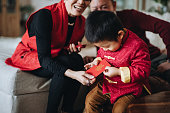 Cute little grandson dressed in red traditional Chinese costume receives red envelops (lai see) with both hands from grandparents joyfully in Chinese New Year