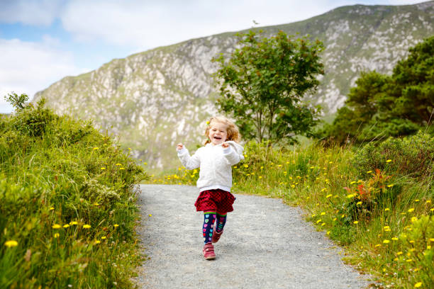 Cute little happy toddler girl running on nature path in Glenveagh national park in Ireland. Smiling and laughing baby child having fun spending family vacations in nature. Traveling with small kids stock photo