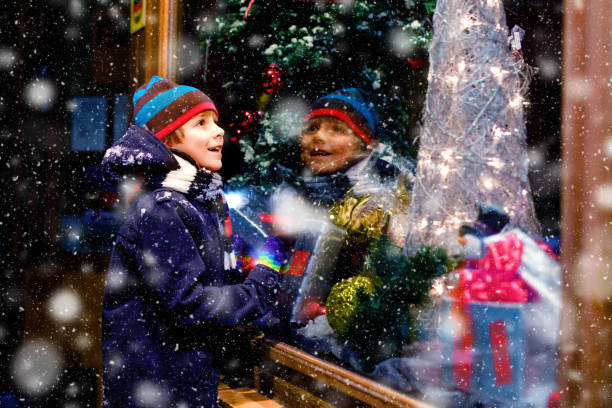 Cute little healthy school kid boy on Christmas market. Funny happy child in fashion winter clothes making window shopping decorated with gifts, xmas tree. Snow falling down, snowfall stock photo