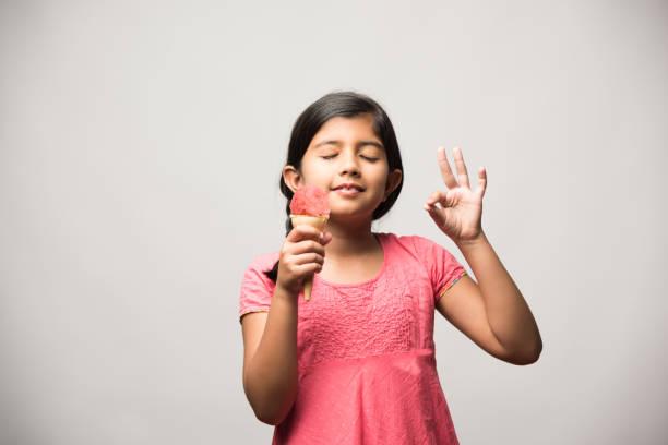 niedliche kleine indische Mädchen essen Eis in Kegel – Foto