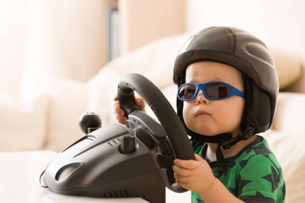 lindo niño en un casco jugando con el volante de la computadora. conductor futuro. preparándose para la conducción profesional. niño conduciendo un coche. niño niño divertido en el interior. chico y un coche. - aprender a conducir fotografías e imágenes de stock