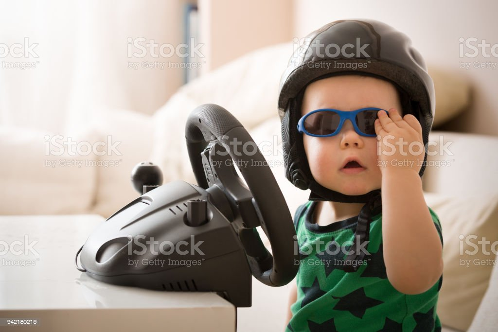 Cute little kid boy in a helmet playing with Computer steering wheel....