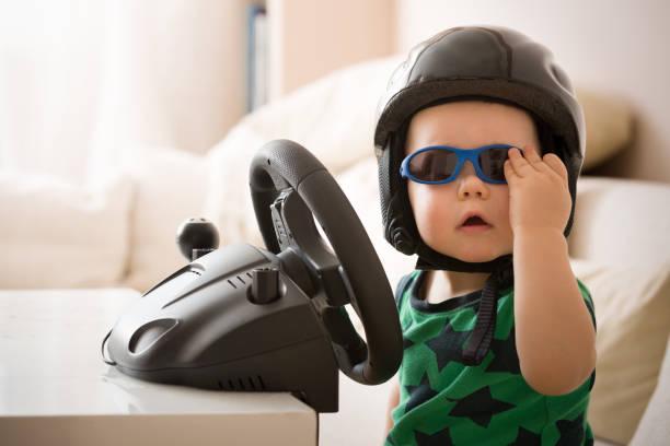 可愛的小男孩在頭盔玩電腦方向盤。未來的驅動程式。為專業駕駛做好準備。孩子開著車。有趣的孩子在室內。男孩和一輛車。 - 人數 個照片及圖片檔