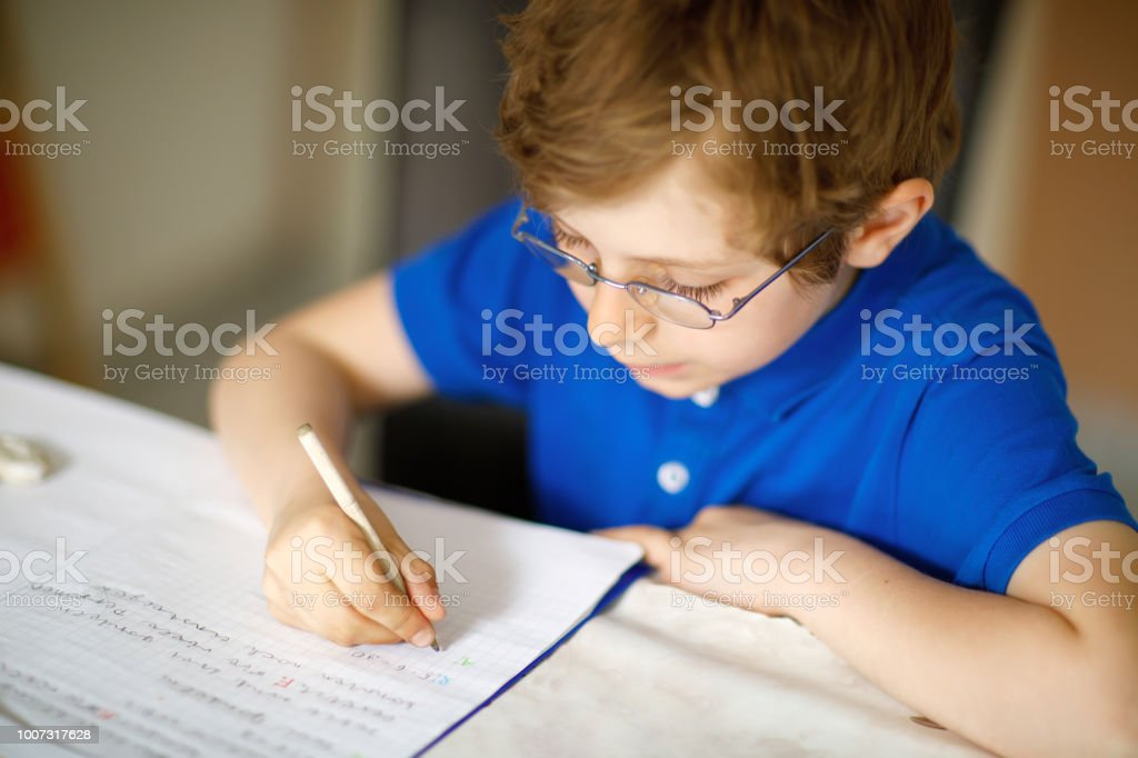 aa13821efd7 Cute Little Kid Boy With Glasses At Home Making Homework Writing ...