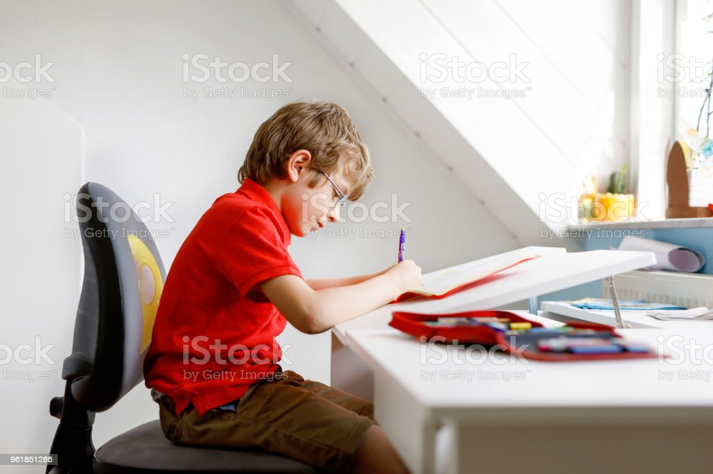 Cute little kid boy with glasses at home making homework, writing letters with colorful pens. stock photo