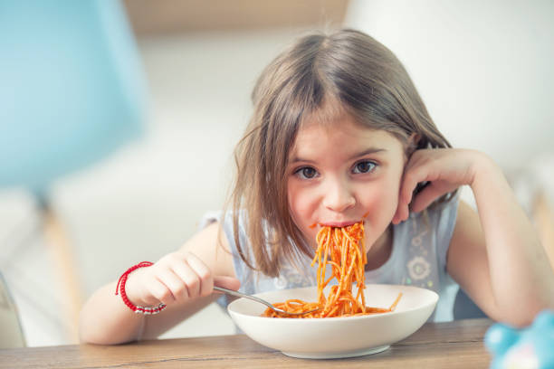 Cute little kid girl eating spaghetti bolognese at home. stock photo