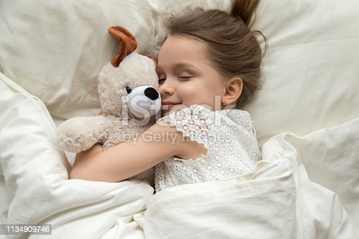 istock Cute little kid girl hugging teddy bear sleeping in bed 1134909746